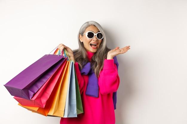Stijlvolle senior aziatische vrouw in zonnebril die gaat winkelen op vakantieverkoop, papieren zakken vasthoudt en glimlacht, staande op een witte achtergrond.