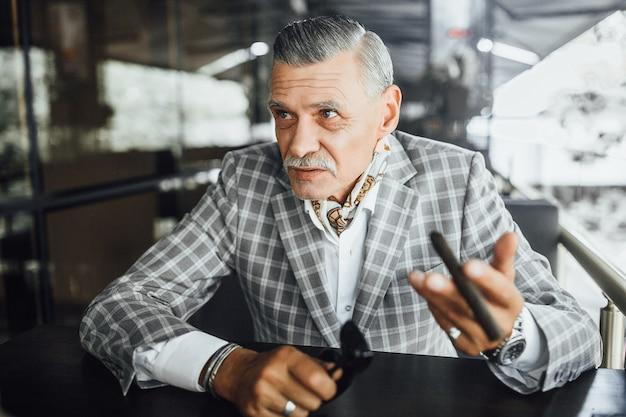 Stijlvolle senior man zit in zomer terrase met cubaanse sigaret
