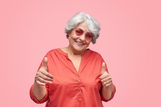 Stijlvolle senior vrouw gebaren duim ups