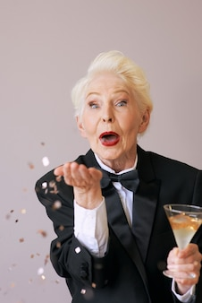 Stijlvolle senior vrouw in smoking met glas met champagne blazende confetti nieuwjaar vieren