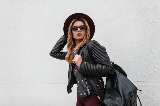 Stijlvolle sexy jonge hipster vrouw in paarse elegante hoed in een vintage leren jas met een modieuze rugzak in trendy zonnebril