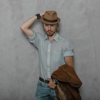 Stijlvolle sexy jongeman hipster in een vintage hoed in modieuze kleding in retro stijl poseren