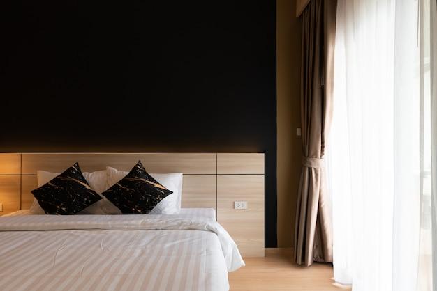 Stijlvolle slaapkamerhoek met houten hoofdeinde en zachte kussens met marineblauwe muur