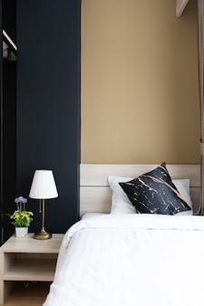 Stijlvolle slaapkamerhoek met houten hoofdeinde met zachte kussens met marineblauw en geel geschilderde muur