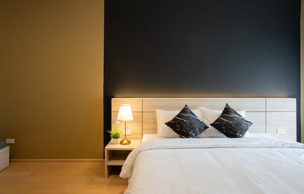 Stijlvolle slaapkamerhoek met houten hoofdeinde zachte kussens met marineblauw en geel geschilderde muur