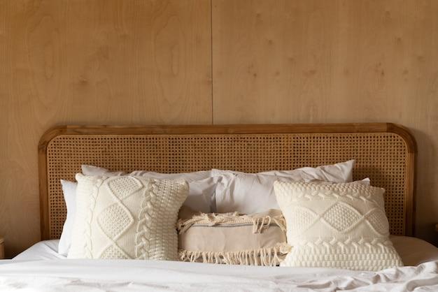 Stijlvolle slaapkamerhoek met rotan hoofdeinde bed en zachte kussendecoratie met multiplex muur gezellig interieur kopie ruimte