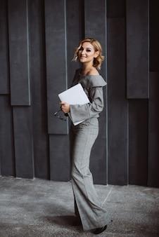 Stijlvolle slimme aantrekkelijke elegante mooie blonde zakenvrouw in een grijs formeel pak en baret kijkt naar een laptop in een grijs kantoor in de loftstijl.