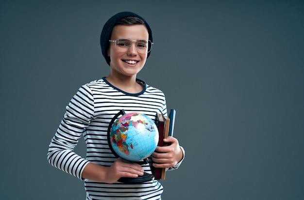 Stijlvolle slimme jongen schooljongen in een hoed en bril houdt een wereldbol en boeken geïsoleerd op een grijs.