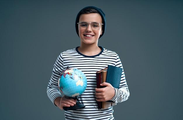 Stijlvolle slimme jongen schooljongen in een hoed en bril houdt een wereldbol en boeken geïsoleerd op een grijze achtergrond.