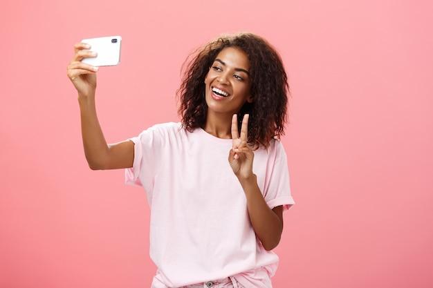 Stijlvolle, sociale, knappe, donkere vrouwelijke student met krullend kapsel die hand trekt met smartphone in de buurt van gezicht selfie te nemen vredesteken tonen aan apparaatscherm terwijl zorgeloos lacht