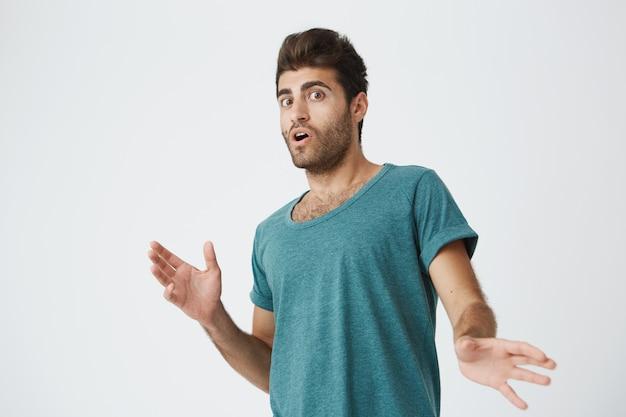 Stijlvolle spaanse jonge ongeschoren man met pop-eyed expressie in blauwe tshirt wordt verrast nieuws gehoord van vriend. lichaamstaal