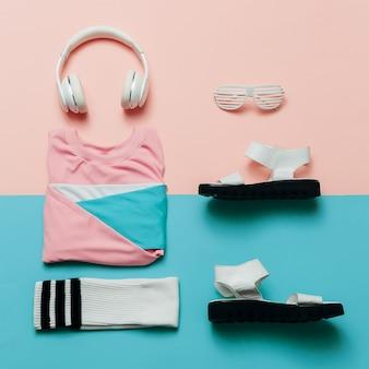 Stijlvolle sportblouse en accessoires. sandalen, zonnebril, oortelefoon minimale stijlvolle kleding fitnessoutfit