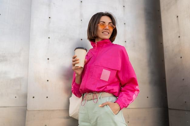 Stijlvolle sportieve vrouw met kort kapsel poseren met koffiekopje