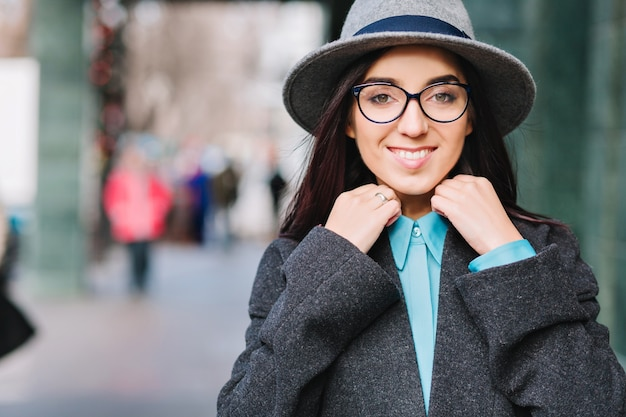 Stijlvolle stad portret jonge mooie vrouw in grijze hoed, zwarte bril lopen op straat in het centrum. luxe jas, modieus model, vrolijke emoties, glimlachen.