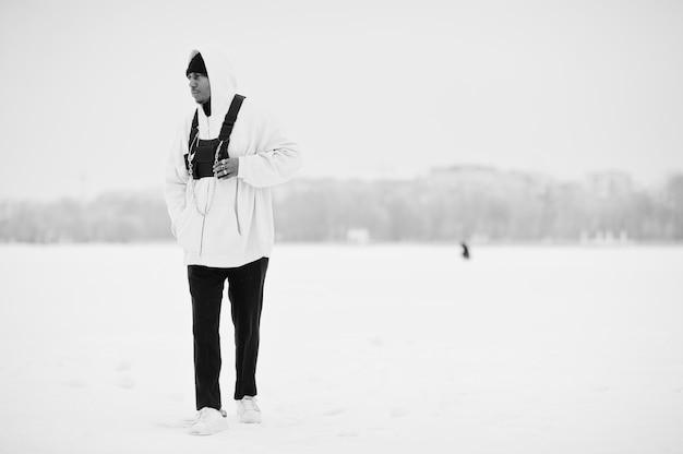 Stijlvolle stedelijke stijl afro-amerikaanse man in roze hoodie gesteld op bevroren meer in de winter.