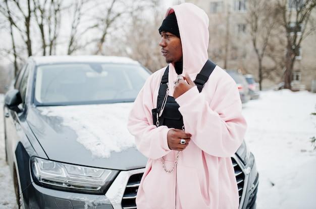 Stijlvolle stedelijke stijl afro-amerikaanse man in roze hoodie gesteld tegen suv-auto in de winter. afro-rapper.