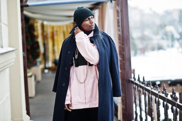 Stijlvolle stedelijke stijl afro-amerikaanse man in zwarte jas en hoed, roze hoodie gesteld op winterdag.