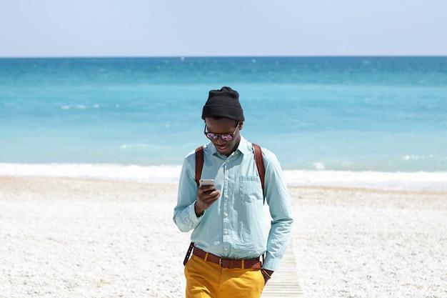 Stijlvolle student met een donkere huidskleurige knapzak die trendy kleding draagt die op de promenade staat na een ochtendwandeling op het woestijnstrand