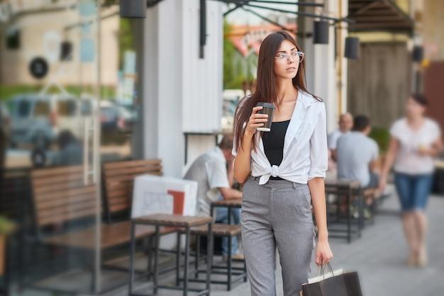 Stijlvolle student wandelen in het centrum van koffie drinken.