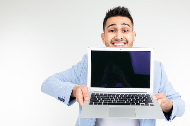 Stijlvolle succesvolle man in een jas toont een laptop scherm met ruimte voor reclame op een witte studio achtergrond met kopie ruimte