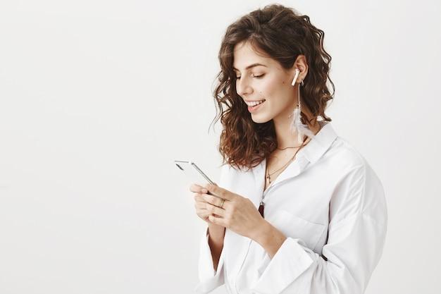 Stijlvolle succesvolle zakenvrouw met behulp van mobiele telefoon en draadloze koptelefoon