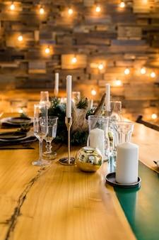 Stijlvolle tafel instelling met brandende kaarsen en kerstversiering. mooie tafel instelling met kerstversiering in woonkamer. feestelijke decoratie op tafel, romantische vakantie-avond