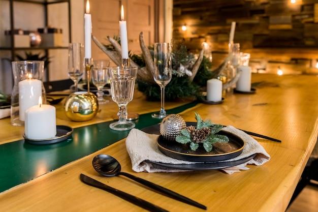Stijlvolle tafel instelling met brandende kaarsen en kerstversiering. stijlvolle kerst interieur. feestelijke inrichting en moderne stijl interieur. warme en gezellige avond in kerst interieur. veel wit