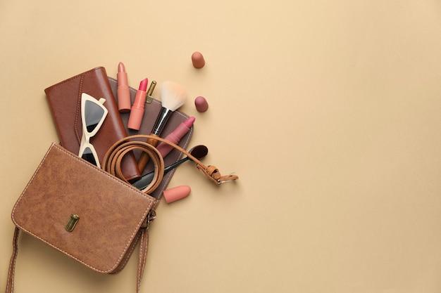 Stijlvolle tas met vrouwelijke accessoires op kleur