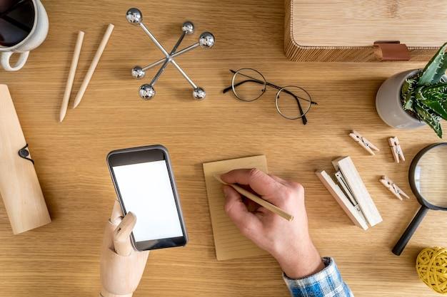 Stijlvolle thuiskantoorsamenstelling van zakenman die mock-up telefoonscherm, kantoorbenodigdheden, cactussen, telefoon, notities, planten en persoonlijke accessoires in plat bedrijfsconcept gebruikt.