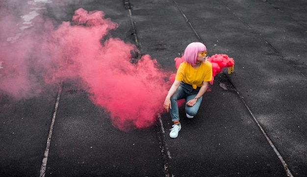 Stijlvolle tiener zit in de buurt van rookgranaat