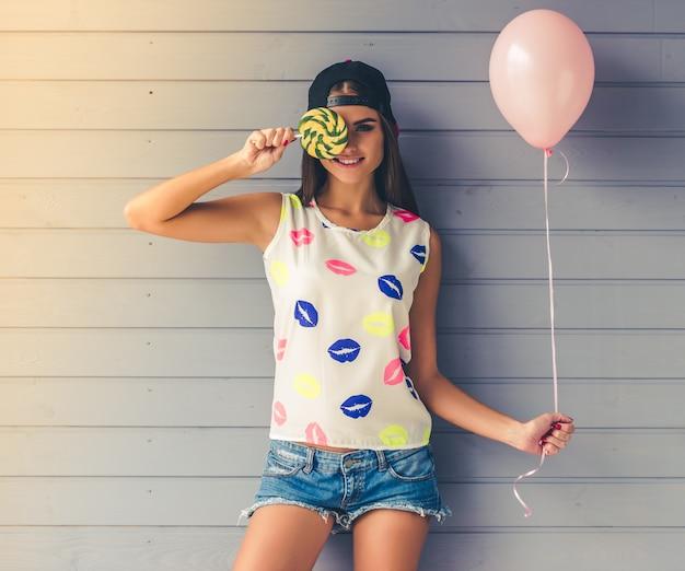 Stijlvolle tienermeisje in cap houdt ballon en lolly.