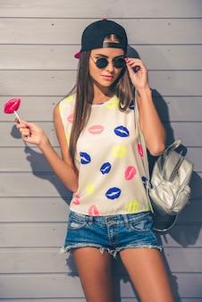 Stijlvolle tienermeisje in zonnebril en pet.