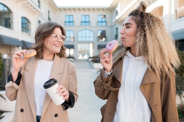 Stijlvolle tieners blij donuts te eten