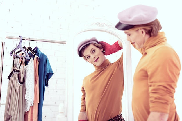 Stijlvolle transgender. aantrekkelijke gender-queer man die tegen de spiegel blijft met heldere doeken en haar kleerkast in de buurt