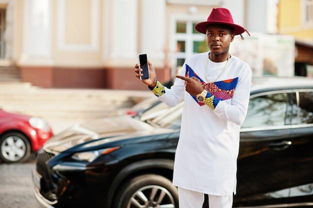 Stijlvolle trendy afro frankrijk man in rode hoed en witte outfit gesteld op herfstdag. zwarte afrikaanse model bedrijfskerel met mobiele telefoon bij handen tegen luxeauto.