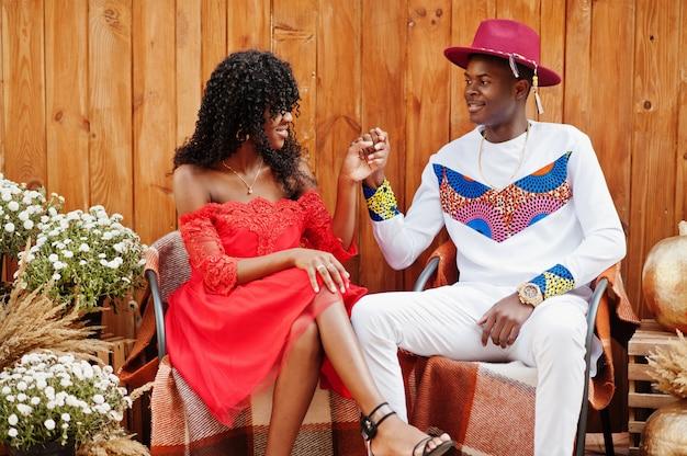 Stijlvolle trendy afro frankrijk paar poseren samen op herfstdag. zwarte afrikaanse modellen in liefde zitten tegen houten decoratie met bloemen en pompoenen.