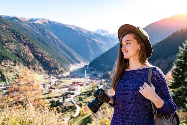 Stijlvolle trendy hipster vrouw reiziger fotograaf met camera in een vilten hoed tijdens het maken van foto's van de bergen en het uzungol meer in trabzon tijdens turkije reizen