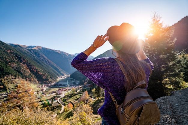 Stijlvolle trendy hipster vrouw reiziger in een vilten hoed met bruine rugzak staat op de bergen en het uzungol meer in trabzon tijdens turkije reizen