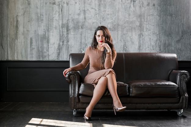 Stijlvolle trendy jonge vrouw met gouden hoge hakken zittend op een gezellige sofa