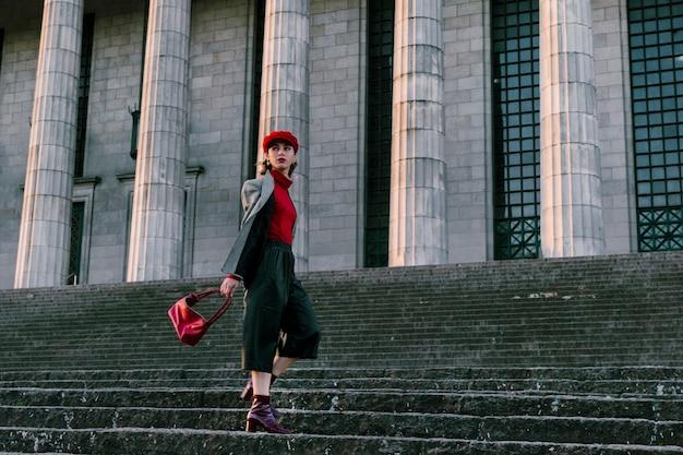 Stijlvolle trendy jonge vrouw met haar handtas staande op trap voor pijler