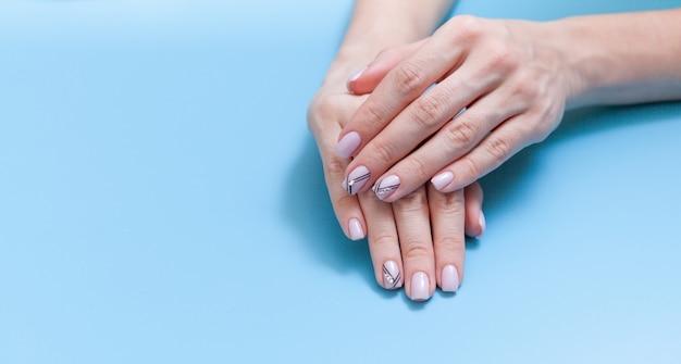 Stijlvolle trendy vrouwelijke manicure. de handen van de mooie jonge vrouw op blauwe achtergrond