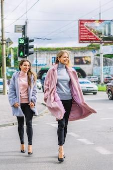 Stijlvolle twee jonge vrouwen in bontjas die de weg kruisen