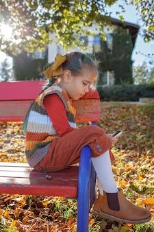 Stijlvolle tween meisje met mobiele telefoon wandelen in de straat jongen en gadgets