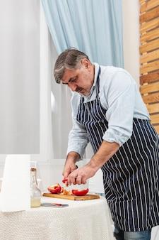 Stijlvolle vader die tomaten snijdt