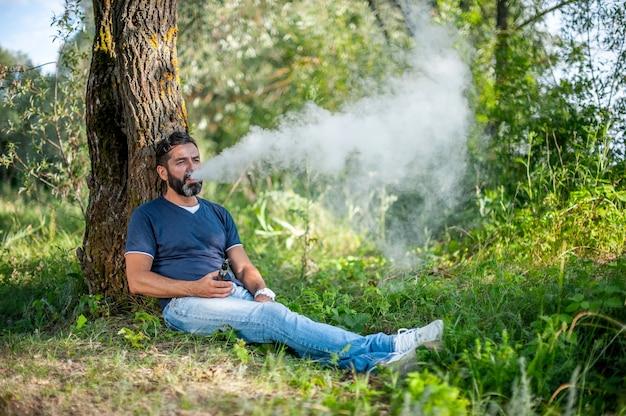 Stijlvolle vape-man blaast een paar een elektronische sigaret op in het bos. knappe man.