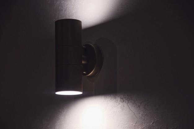 Stijlvolle verhelderende moderne lamp op witte getextureerde muur in interieur. gloeiende chromen led-lamp op grijze muur. vrije ruimte en donkere streep op de achtergrond voor inscriptie. ruimte kopiëren voor site of banner