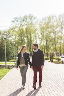 Stijlvolle verliefde paar hand in hand op straat, vrouw is zwanger.