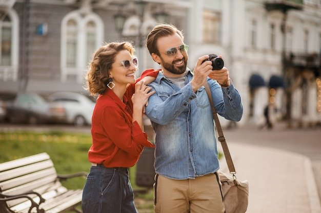 Stijlvolle verliefde paar wandelen omarmen in straat op romantische reis en het nemen van foto Gratis Foto