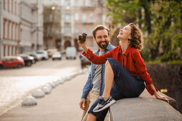Stijlvolle verliefde paar zittend op straat op romantische reis, foto nemen