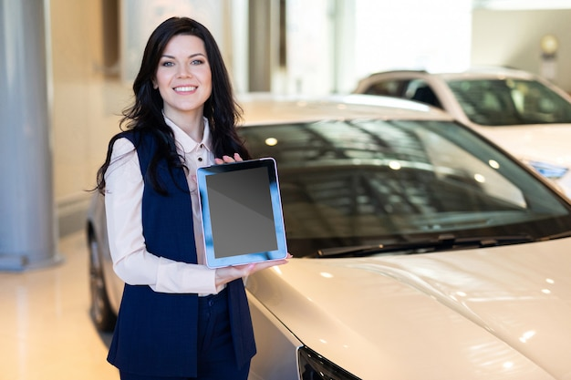 Stijlvolle verzekeringsagent die zich dichtbij de auto bevindt en een tablet houdt